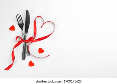 Beautiful cutlery set, hearts and red ribbon on white background, flat lay with space for text. Valentine's Day dinner
