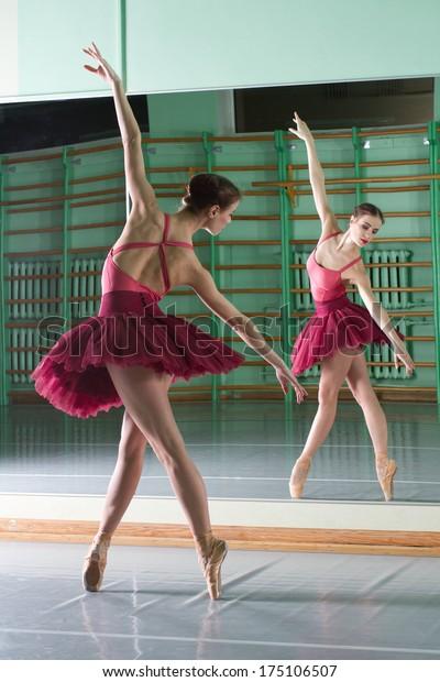 beautiful dancer ballerina is doing exercises in ballet class
