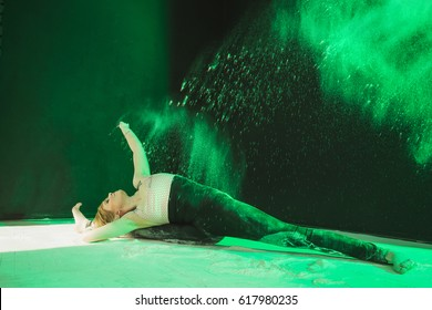 A beautiful dancer or gymnast in a cloud of flour. Yoga woman sitting on a twine. White powder and young athletic girl.