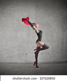 Beautiful dancer holding a red feather boa