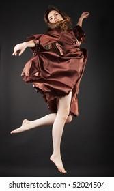 Beautiful dancer jumping on dark background