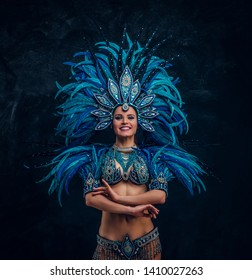 Beautiful dancer is standing crosses her hands. She is wearing blue feather costume.