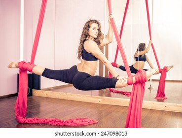Beautiful dancer training with aerial silk in a fitness studio