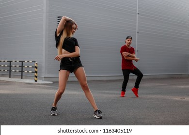 Beautiful dancer woman in black fashion clothes dancing on the street. dancer man on the background