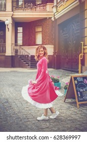 Beautiful dancing girl in a pink dress looks around the city street.
