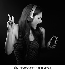 Beautiful dancing young woman listening the music, showing v sign by hand in wireless headphone and holding mobile phone on dark background. Black and white