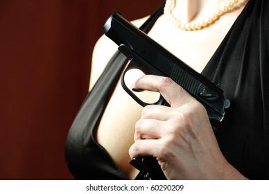 Beautiful and dangerous woman: gun, breast, pearls