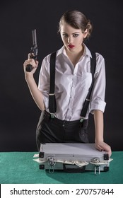 Beautiful and dangerous. Young female gangster holding the gun. isolated on dark background. On the green table a bag of cash.