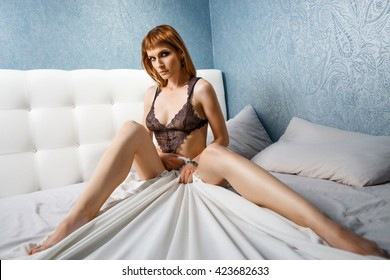 Beautiful dark blonde sexy girl in lace lingerie sitting on bed