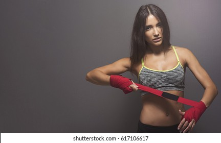 Beautiful dark haired fitness model in workout gear and wrapping her hands with boxing wraps and looking seriously at the camera.