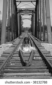 A beautiful dark haired girl in a dress kneels between the rails of a railroad track with a trestle bridge in the background.
