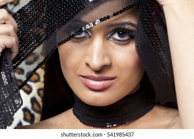 Beautiful dark haired middle eastern woman against block grey background