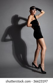 beautiful dark haired model in black dress with her distorted shadow on the wall