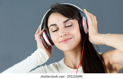 Beautiful dark haired smiling woman wearing headphones and listening music on grey background.