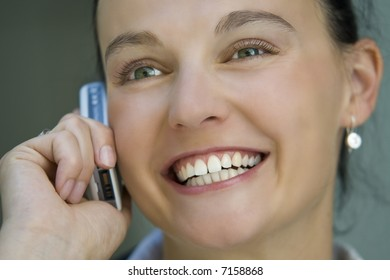 A beautiful dark haired woman talks happily on her mobile phone.