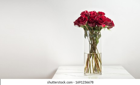 Beautiful dark red roses, flowers in a vase, side view, vertical, white background