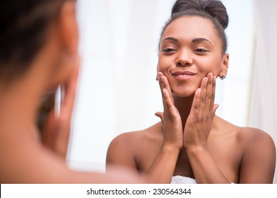 Beautiful dark skinned girl in white towel bringing face cream looking at mirror admiring  herself  touching cheeks smiling  isolated on white background