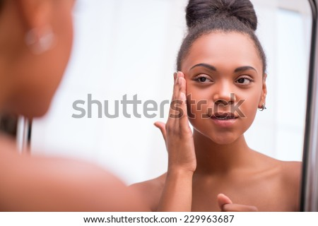 6c31753a1bd Beautiful dark skinned girl in white towel bringing face cream looking at  mirror isolated on white