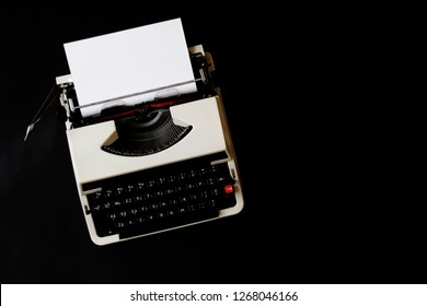 beautiful dark vintage top view close up photo flat lay photo of old typewriter machine with white blank paper in it on black background with copy space
