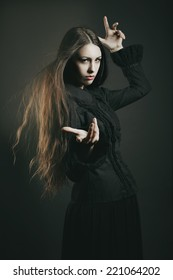 Beautiful dark witch casting a spell . Halloween and fantasy studio shot