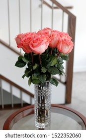 Beautiful darker pink rose flowers with dark green leaves in a glass crystal vase on a living room side table. Pink roses flower bouquet in a clear tall crystal vase on a round table near a stairwell.