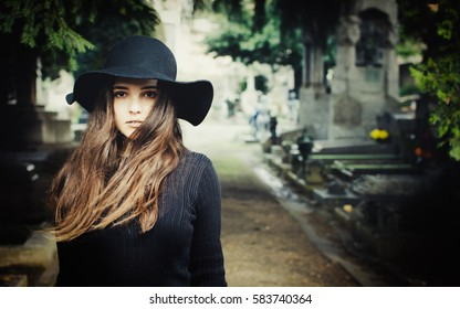 Beautiful dark-haired girl alone at cemetery, wearing black hat.