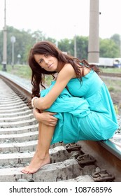 The beautiful dark-haired girl in a blue dress sits on rails