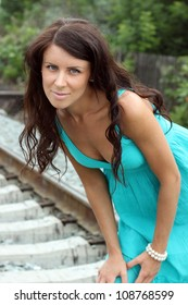 The beautiful dark-haired girl in a blue dress