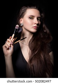 Beautiful dark-haired girl on a black background with a delicate makeup, holding a brush for makeup