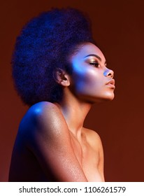 """Beautiful dark-haired girl in profile on a claret background. Bright makeup and curvy hair in the style of """"Afro"""". Color filters."""