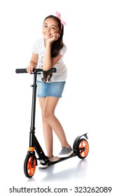 Beautiful dark-haired girl in a short denim skirt riding her scooter.-Isolated on white background