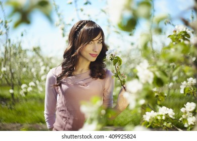 beautiful dark-haired girl in white flowering trees in spring, soft focus