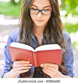 Beautiful dark-haired serious girl in jeans jacket and glasses reads red book against summer green park.