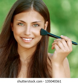 Beautiful dark-haired smiling young woman treats her face with brush, against background of summer green park.