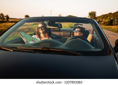 Beautiful dark-haired young women in sunglasses are sitting in a black cabriolet on a sunny day. One of them keeps map in her hands.