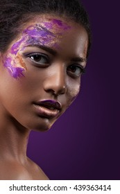 A beautiful dark-skinned woman with paint on his face. Beauty, fashion, portrait. Creative make-up close-up.