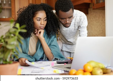 Beautiful dark-skinned young female with Afro hairstyle having worried look while managing family budget together with her husband in kitchen, paying gas and utility bills online, using laptop pc