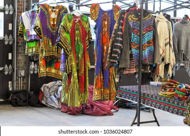 Beautiful Dashiki shirts and dresses for sale, along with other colorful textiles on a rack at the market. Throwback to 1970's urban style.