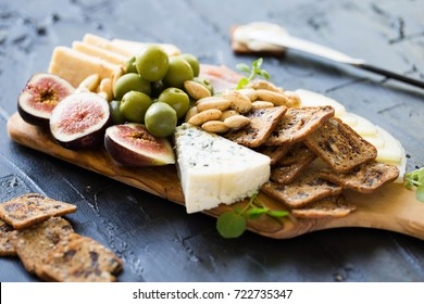 Beautiful Date Night Cheese Board with Sharp Cheddar Manchego and Blue Cheese Figs Crackers Green Olives and Prosciutto on Dark Background with Knife