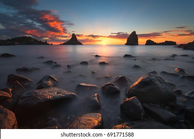 A beautiful dawn photographed at the sea stacks of Acitrezza, in Italy.