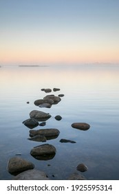 Beautiful dawn seascape with the steaming seawater and stepping stone rocks in the front