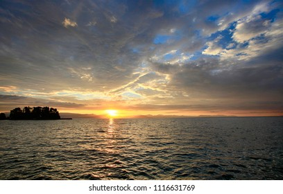 Beautiful dawn. The sun rises above the sea with beautiful clouds off the coast of the island of Corfu