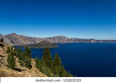 Beautiful day at Crater Lake National Park with a beautiful clear day and a deep blue color in the sky and lake