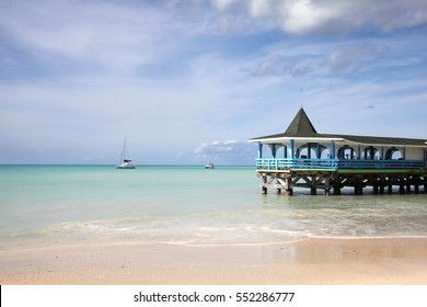 Beautiful day with a view out to sea & the pier of Runaway Beach, Antigua, Caribbean.
