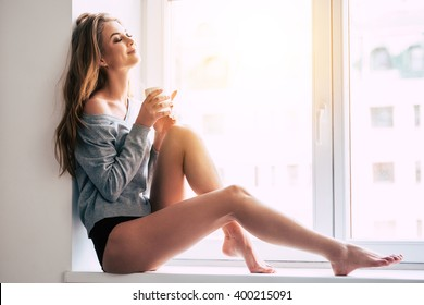 Beautiful daydreamer. Beautiful young woman holding coffee cup and keeping eyes closed with smile while sitting at windowsill at home