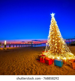 Beautiful decorated Christmas tree on the beach at night of twilight sky with blur background, HAPPY NEW YEAR.