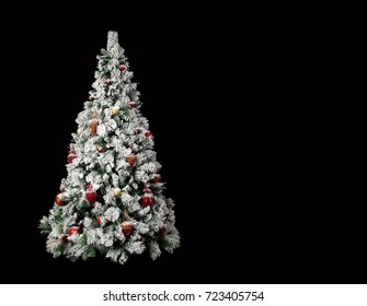 Beautiful decorated christmas tree with a lot of snow on it in front of a black background