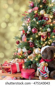 Beautiful decorated Christmas tree with sparkling  lights, baubles, teddy bears and red gifts. Defocused gold bokeh background.