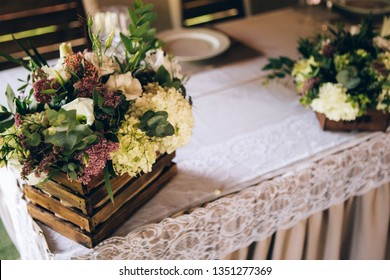 Beautiful decorated elegant wedding table for dinner with floral white bouquets, candlesticks and a white tablecloth glasses and porcelain plates