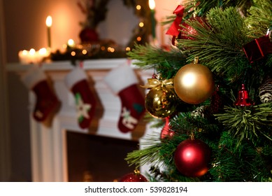 Beautiful decorated fireplace and Christmas tree at cottage. A rich christmas tree with lots of hanging toys and a candled fireplace blurred on the background.
